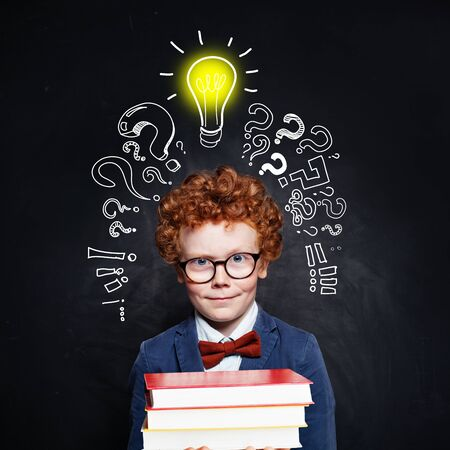 Smiling child with lightbulb and books on blackboard background