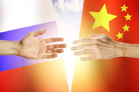Two hands stretch towards each other against the background. Hands people against the backdrop flags Russia and China
