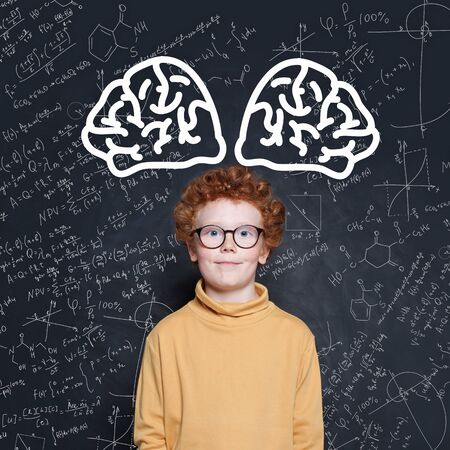 Kid boy with red hair standing against blackboard with science formulas