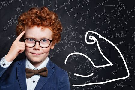 Clever little boy with red ginger hair on science background. Learn science concept Reklamní fotografie