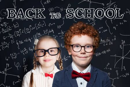 Cute children in classroom on chalkboard background. Back to school concept