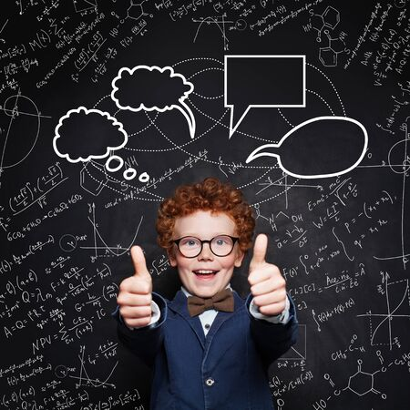 Happy smart child student on blackboard background with science and maths formula