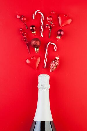 Christmas concept. Sparkling wine bottle and colorful red Xmas decorations on red background