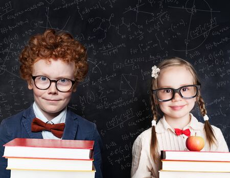 Back to school concept. Smart kids portrait. Little girl and boy student holding book and apple fruit against blackboard background with science and maths formulas Stockfoto