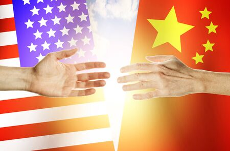 Two hands stretch towards each other against the background. Hands people against the backdrop flags USA and China