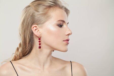 Weibliches Profil. Ohr mit modischen goldenen Ohrringen mit rotem Granat auf weißem Hintergrund