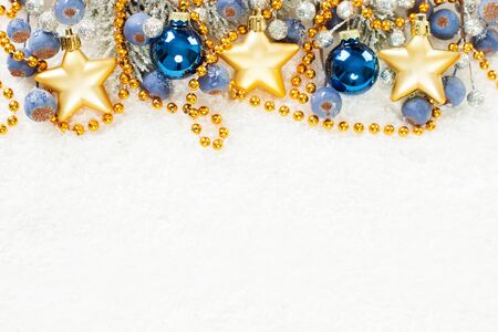 Christmas composition border with blue, gold and silver decor on white snow background