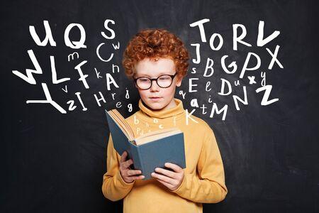 Child reading. Kid school boy holding book on black background