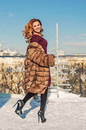 Fashion portrait of beautiful woman in winter coat and high heels shoes