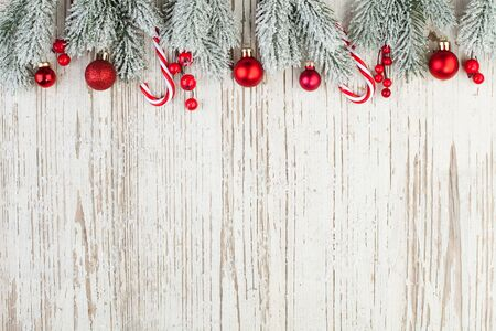 Beautiful Christmas composition border on white wooden background. Red holly berries, baubles and green fir branch. Minimal Xmas flat lay top view on wood texture with copy space Reklamní fotografie
