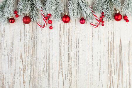 Schöne Weihnachtszusammensetzungsgrenze auf weißem hölzernem Hintergrund. Rote Stechpalmenbeeren, Kugeln und grüner Tannenzweig. Minimale Weihnachtsflache Draufsicht auf Holzstruktur mit Kopierraum Standard-Bild