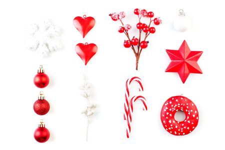Red Christmas decorations isolated on white. Red holly berries, snowflake, glass baubles on white background, top view