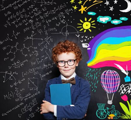 Redhead kid boy in glasses holding book with empty cover on chalkboard background with creative scetch
