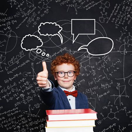 Cute clever kid boy with empty speech clouds bubbles on science formulas background