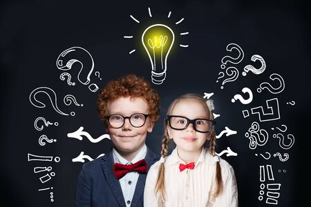 Brainstorming and idea concept. Smart successful children girl and boy student with lightbulb on blackboard background