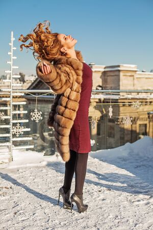 Beautiful pretty winter woman with red curly hairstyle outdoor Zdjęcie Seryjne
