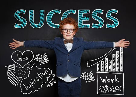 Young boy in blue suit against success concept Zdjęcie Seryjne