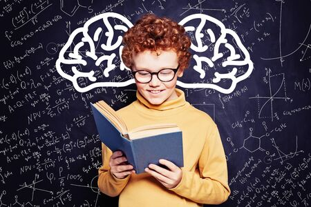 Cute child boy reading a book, imagination, creativity and brainstorming concept
