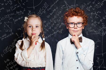 Intelligentes Denken der kleinen Kinder. Kleiner Junge und Studentin auf Tafelhintergrund mit Wissenschafts- und Mathematikformeln