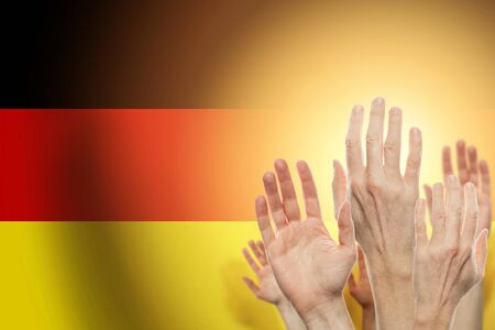 People raising hands and flag Germany on background. Patriotic concept