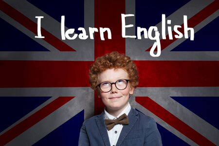 Pretty child boy in school uniform and glasses against the UK flag background. Redhead kid learning English