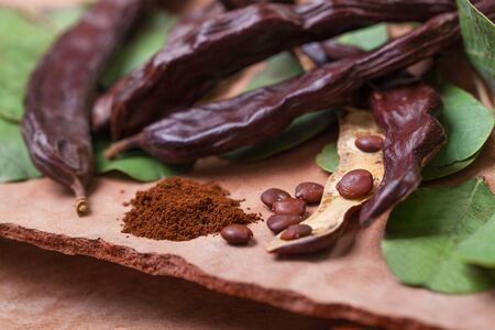 Carob. Organic carob pods with seeds and leaves on tree bark table. Healthy eating, food background. Zdjęcie Seryjne