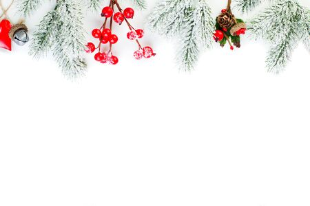 Beautiful Christmas border on white. Green Xmas fir branch, red holly berries and Xmas decor isolated on white background Zdjęcie Seryjne