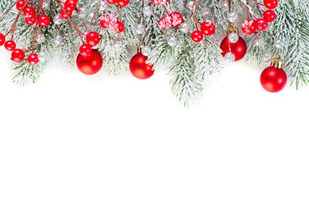 Christmas concept. Xmas border composition with red glass baubles, holly berries and green fir branch isolated on white background. Xmas flat lay top view
