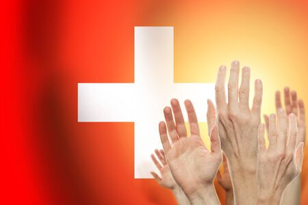 People raising hands and flag Switzerland on background. Patriotic concept 免版税图像