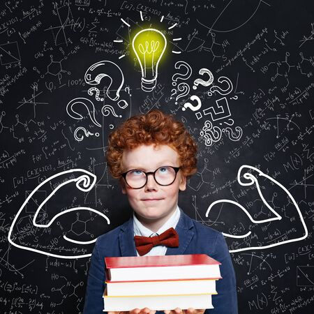 Little boy student thinking and looking at lightbulb on blackboard background