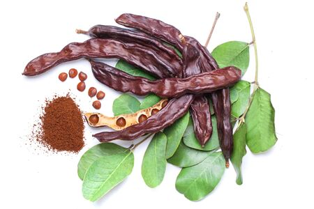 Carob beans with carob powder. Healthy organic sweet carob pods with seeds and leaves on white background 免版税图像