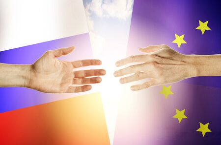 Two hands stretch towards each other against the background. Hands people against the backdrop flags Russia and European Union Stok Fotoğraf - 131957848