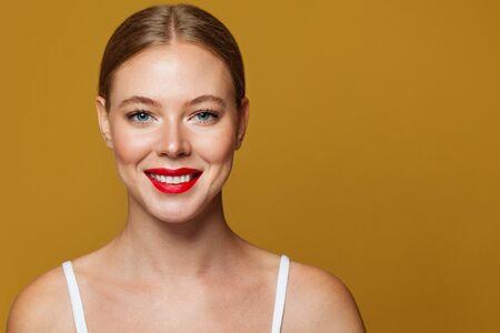 Happy female face on yellow banner, close up portrait. Friendly smile, healthy clear skin Foto de archivo