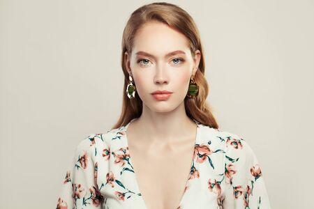 Pretty elegant woman fashion model wearing golden chain earrings on white background Reklamní fotografie