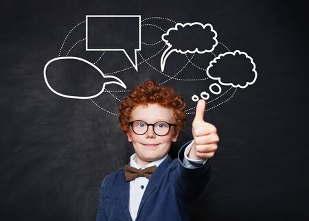 Funny little boy and empty speech clouds bubbles on chalkboard background