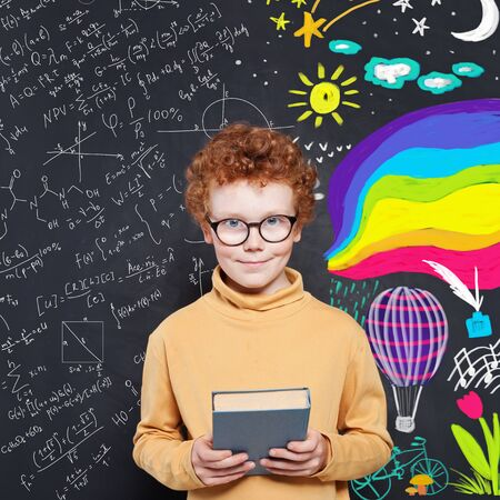 Cheerful smiling little boy with book on chalkboard background. Child looking at camera. School and education concept