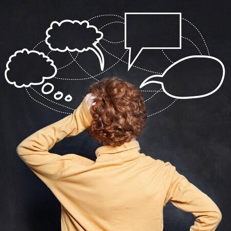 Thinking child looking at empty speech clouds bubbles on chalkboard background