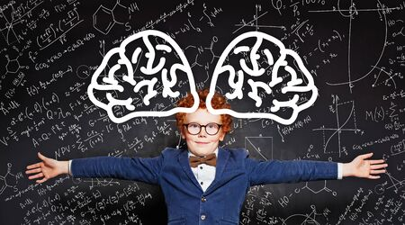 Happy kid embracing on blackboard background with science formulas and brain pattern