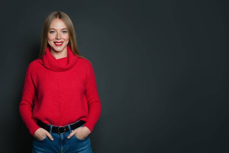 Happy woman in red pullover standing against gray wall background Banco de Imagens