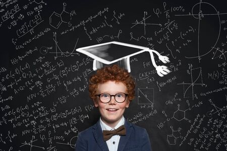 Happy kid wearing graduation hat, glasses and student uniform on science background