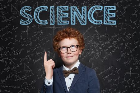 Smart confident kid boy with red hair pointing up at science inscription on chalkkboard