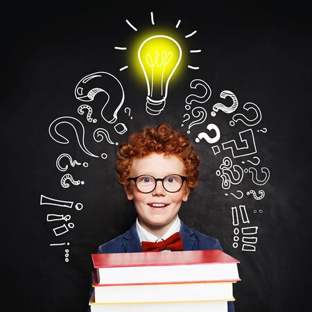 Redhead student child with lightbulb on blackboard background. Idea concept