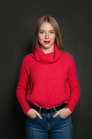 Cute young woman in red pullover on gray background Banque d'images - 135491076