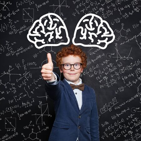 Happy child boy smiling and showing thumb up on science background