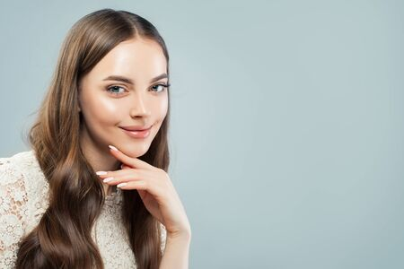 Beautiful woman smiling on light blue background Stock Photo