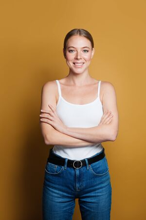 Smiling woman with crossed arms on yellow background 版權商用圖片