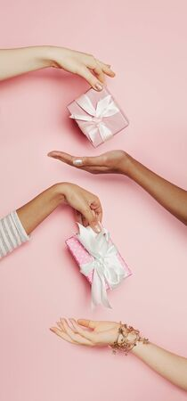 Many women hands with gifts. Abstract luxury holiday and sale concept on pink background 版權商用圖片