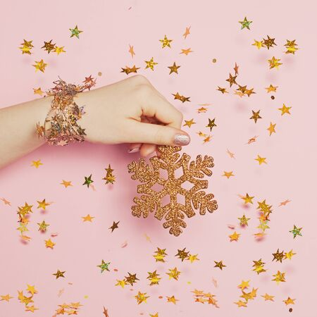 Christmas decoration background. Gold Xmas decoration snowflake in hand on pink background with gold blowing confetti stars