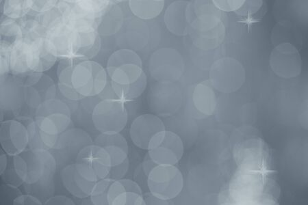 Silver bokeh abstract texture. Gray defocused background with blurred bright light glitter and stars