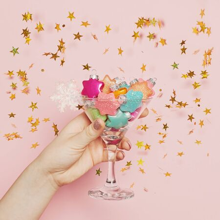 Christmas background, toast and chin-chin concept. Xmas glass with decoration in hand on pink background with gold glitter sparkle confetti stars